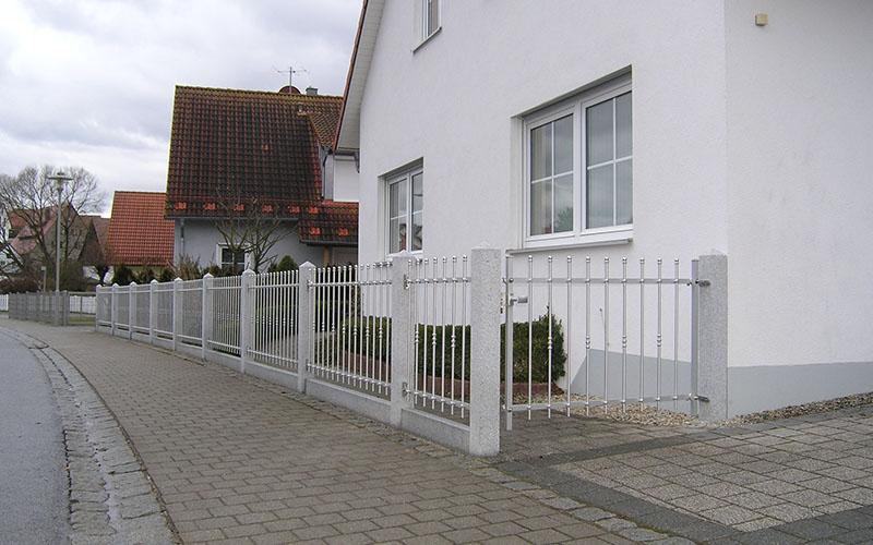 Tor und Zaun zwischen Granitsäulen